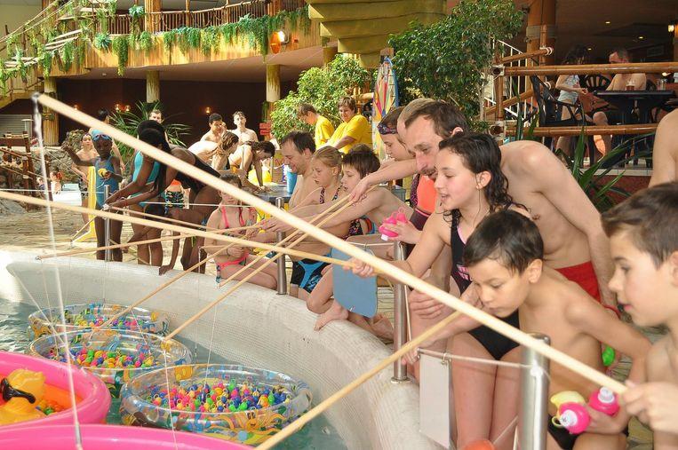Heel wat kinderen staan geconcentreerd rond het zwembad om eendjes te vissen.