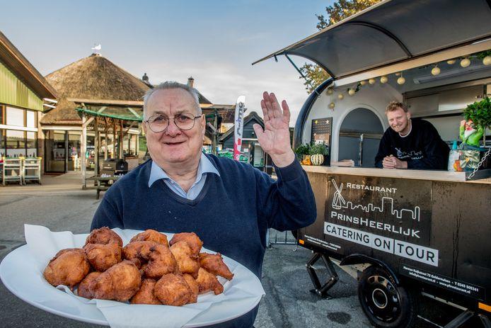 Arie van Westrienen met zijn 'okkiebollen', in de kraam kijkt Leon Prins mee.