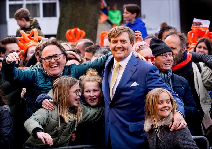 Koning Willem Alexander die twee meisjes verrast met een omhelzing in Zwolle (2016), met rechts zijn dochter Ariane. ,,Een symbolisch moment voor wat Koningsdag nu is. Het is een verbindende dag'', vindt royaltywatcher Justine Marcella.
