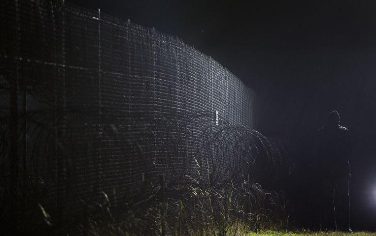 Een vluchtelingen loopt langs het hek dat hem scheidt van de Eurostar, de trein waarmee vluchtelingen hopen in Engeland te komen. Beeld Freek van den Bergh