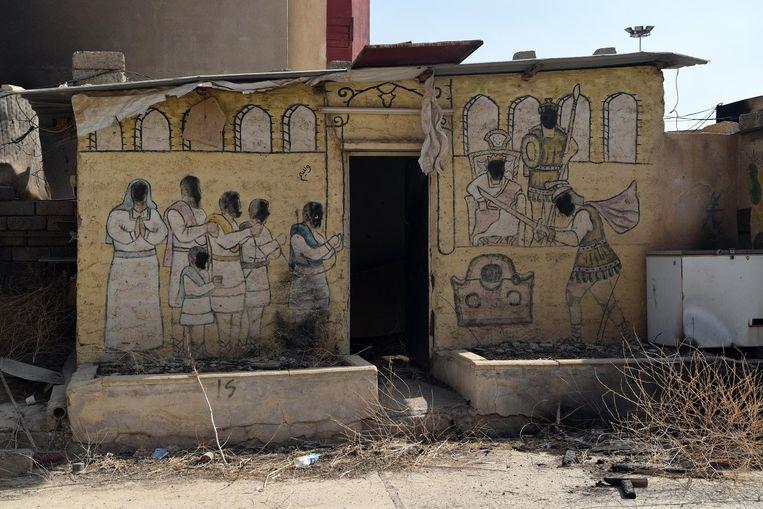 Gezichten van een Bijbels tafereel op de zijkant van een kerk zijn zwart gemaakt door IS toen zij een voornamelijk door christenen bewoond dorp bezetten. Beeld getty