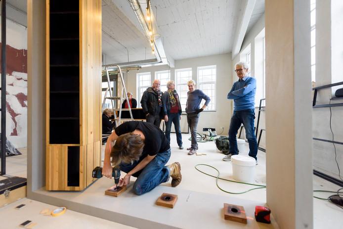 Nico van der Henst, Marianne van Buul met Jac Duijf en Chris van Lenteren (vlnr) in de woning van Duijf in CPO Twee op het NRE-terrein in Eindhoven.
