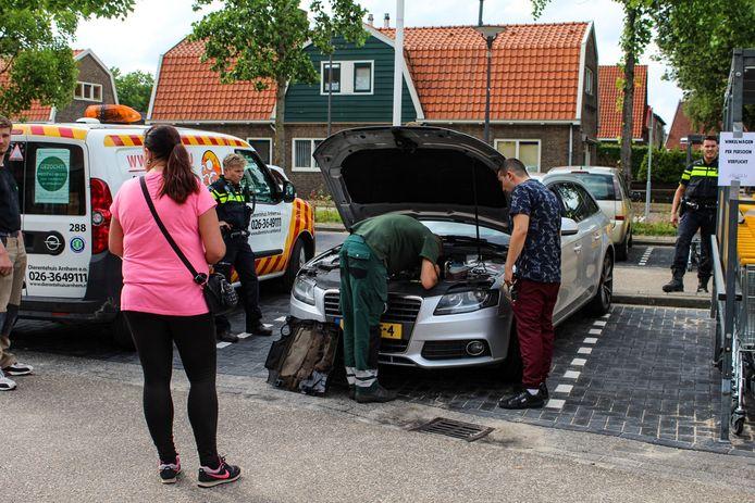 Een medewerker van de dierenambulance probeert de kitten te bevrijden uit het motorblok van een auto.