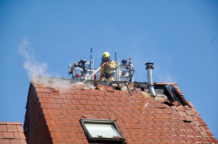 De brandweer bestrijdt het vuur op het dak van het huis in Arnhem.