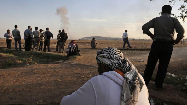 Turkse Koerden kijken vanuit de verte naar het bombardement op Kobani Beeld ap