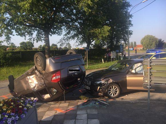 Door de botsing belandde een auto op het dak.