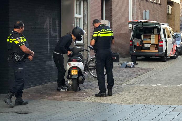 De politie bekeurt een scooterrijder in het centrum van Enschede.