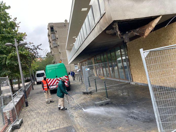 Arbeiders spoelen de roetplekken van het trottoir voor de crèche. Het gebouw raakte beschadigd door de vlammen.