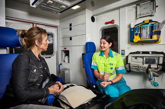 Een ambulancechauffeur  (links) en ambulanceverpleegkundige (in uniform) doen voor hoe een sollicitatiegesprek in een ambulance er uit ziet.
