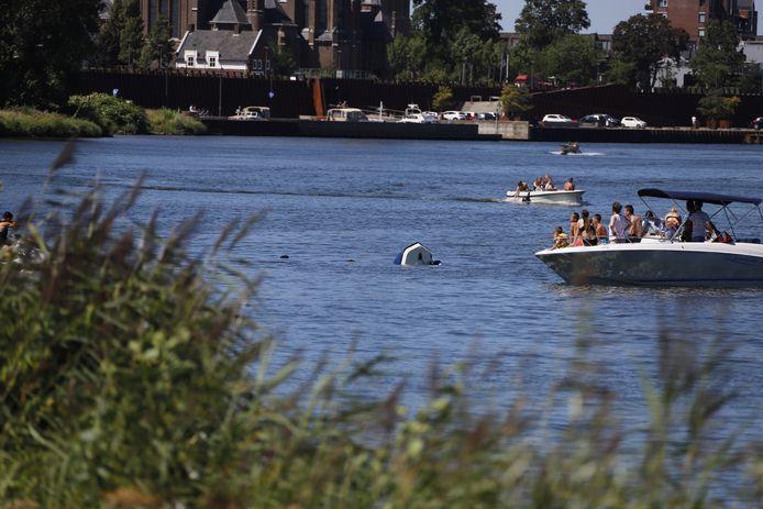 De boot steekt nog net boven het water uit terwijl omstanders toekijken.