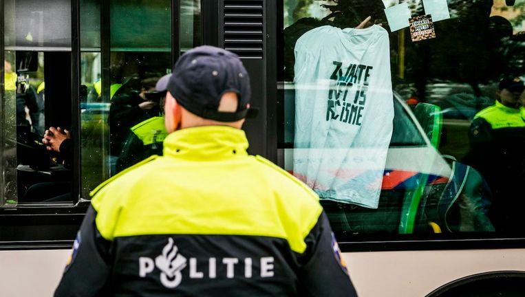 Een bus met tegenstanders van Zwarte Piet komt onder politiebegeleiding aan bij het politiebureau in Maassluis Beeld ANP