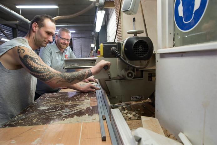 Gerard van den Bergh (rechts) coacht een collega bij het vervaardigen van glaslatten.