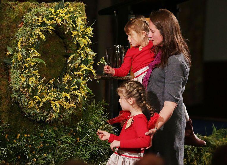 Familieleden van slachtoffers van de ramp bij de herdenking vrijdag in Australië. Beeld null