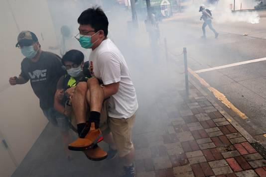 Demonstranten in Hongkong vluchten voor een traangaswolk.