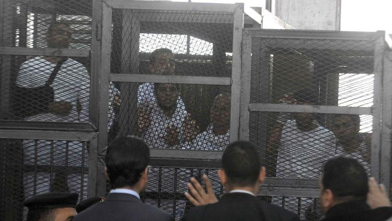 Journalisten van Al-Jazeera tijdens een rechtszaak in Caïro. Beeld getty