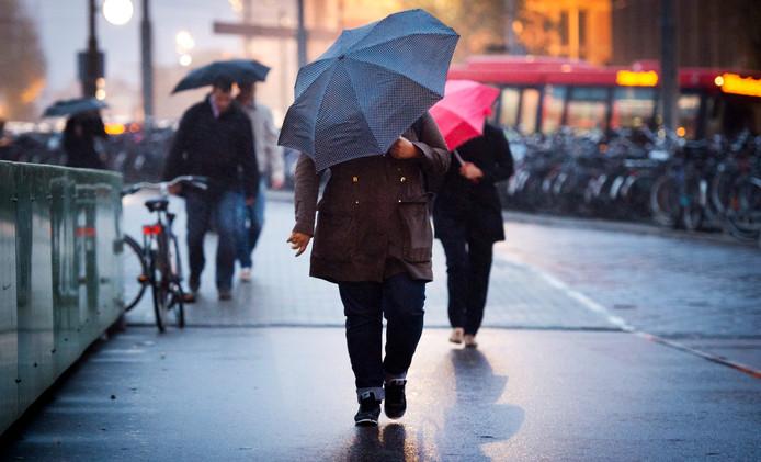 Voetgangers trotseren slecht weer in het centrum van Amsterdam.