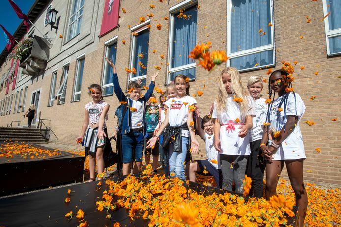 Kinderen van de Airborneschool te Renkum tussen de eerder gegooide goudsbloemen.