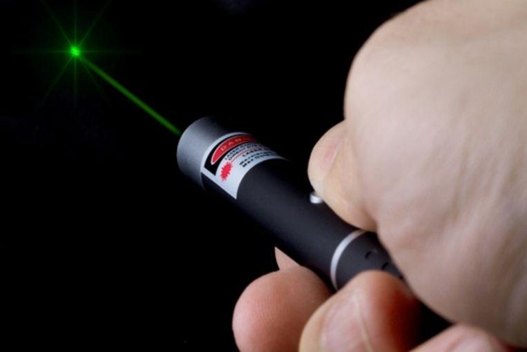 Een man gebruikt een laserpen, illustratiebeeld.