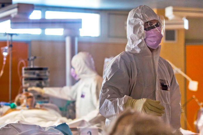 Personeel op een intensive care verzorgt een doodzieke coronapatiënt.