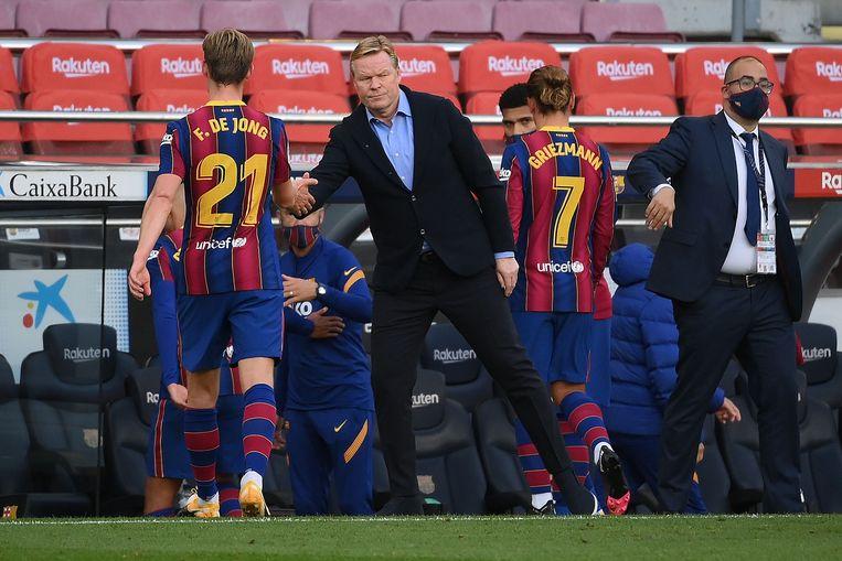 Barcelona-coach Ronald Koeman geeft een handje aan Frenkie de Jong, na het laatste fluitsignaal van El Clasico (1-3).  Beeld AFP