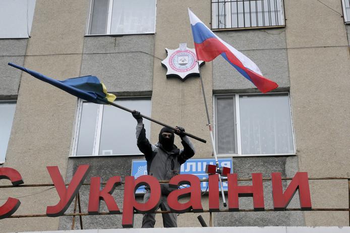 Een pro-Russische verwisselt de Oekraïense vlag op het politiebureau van Horlivak voor een Russisch vaandel.