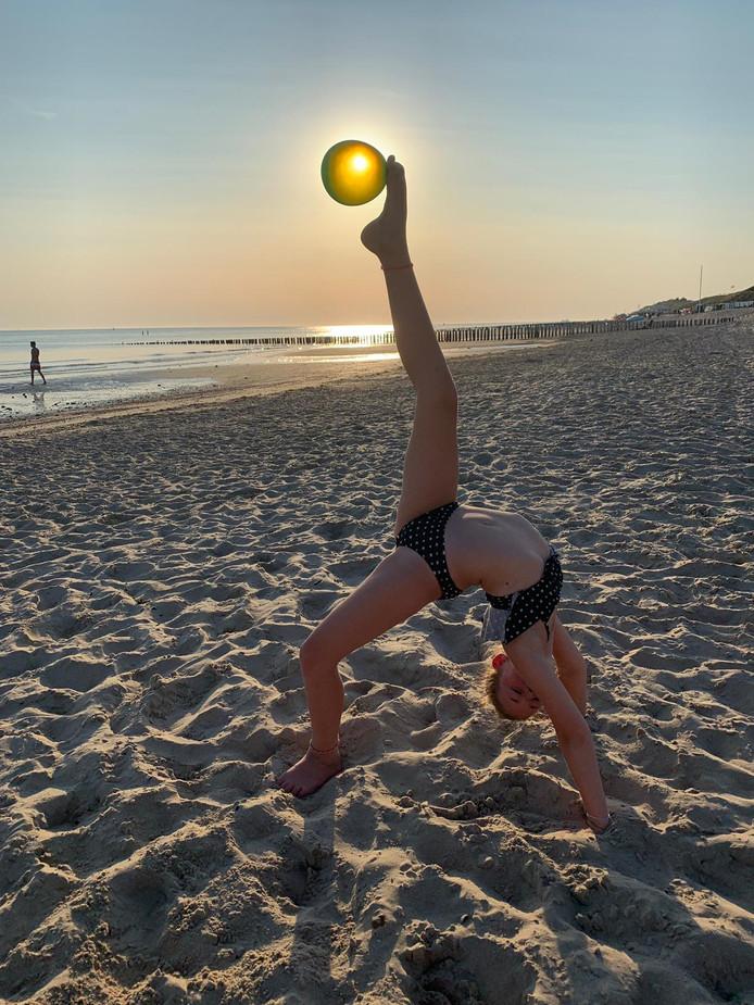 Op het strand van Zoutelande maakt Guusje Hopstaken een bruggetje met een ballon tussen haar tenen. Goede timing: de ballon zit precies voor de zon!