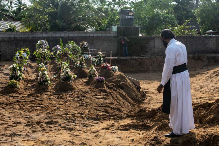 Een priester tijdens een groepsbegrafenis van slachtoffers van de bomaanslag op de St Sebastian-kerk in Negombo, Sri Lanka. Beeld Getty Images