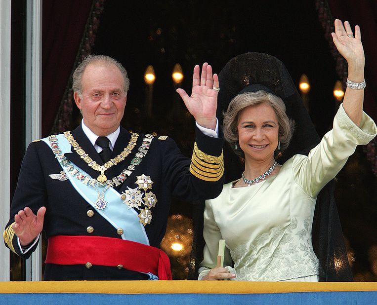 Koning Juan Carlos en zijn vrouw koningin Sofia van Spanje zwaaien naar het volk vanaf het balkon van het koninklijk paleis in Madrid, mei 2004.   Beeld AFP