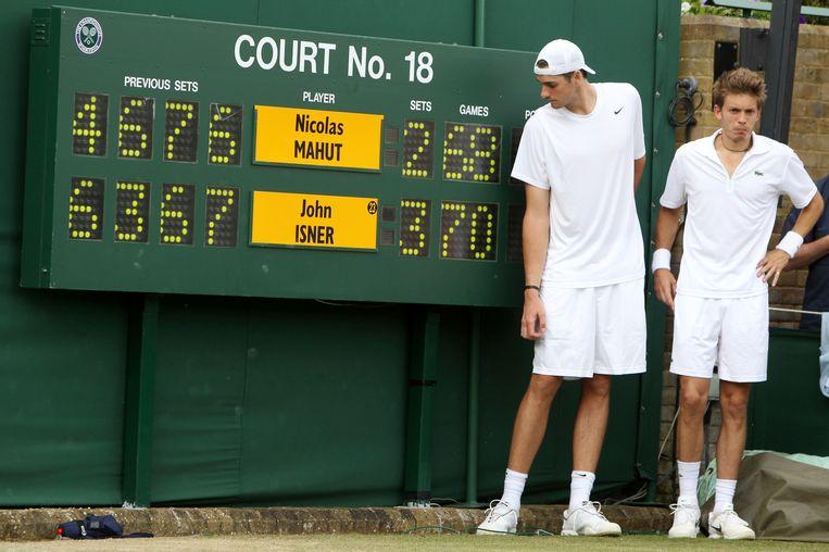 De Amerikaanse tennisser John Isner en Fransman Nicolas Mahut poseren naast het scorebord na afloop van hun marathonpartij op Wimbledon in 2010. Beide tennissers stonden destijds 11 uur en 5 minuten - verspreid over drie dagen - op de baan. Isner won uiteindelijk de partij door de vijfde set met 70-68 naar zich toe te trekken. Beeld AP