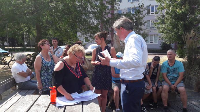 Wethouder Roeland van der Zee op bezoek bij een groep bewoners in in de Arnhemse wijk Malburgen West.