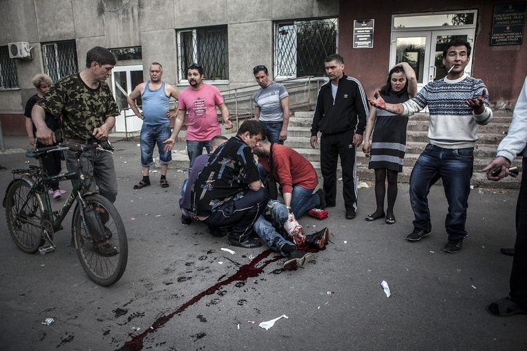 Inwoners van Krasnoarmisk helpen een gewonde man. Beeld epa