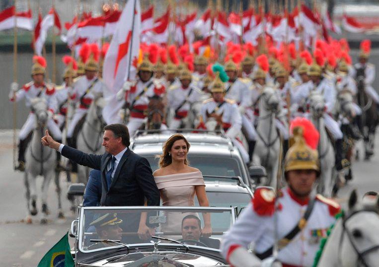 De nieuwe Braziliaanse president Jair Bolsonaro en zijn vrouw Michelle laten zich toejuichen in de hoofdstad Brasilia. Beeld AFP