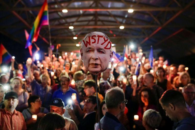 Betogers houden een foto omhoog van de partijleider Jaroslaw Kaczynski van de Recht en Rechtvaardigheidspartij (PiS), op zijn gezicht staat 'schande' geschreven. Beeld Reuters