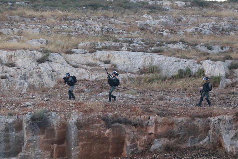 Israëlische soldaten vuren traangasgranaten af op Palestijnse betogers bij de nederzetting Beit El, op de Westelijke Jordaanoever. Beeld Anadolu Agency via Getty Images