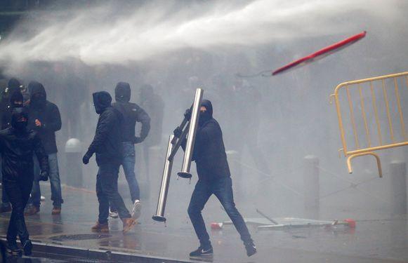 Een demonstrant gooit met een barricade naar de politie.