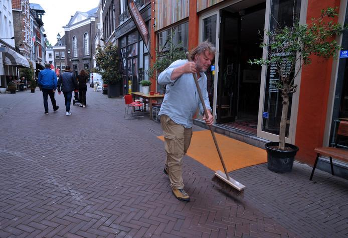 Johan van Hilten van JouWinkel op de Voorstraat veegt zijn stoep.