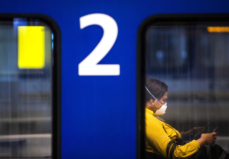 Een reiziger met een mondkapje op station Den Haag Centraal.