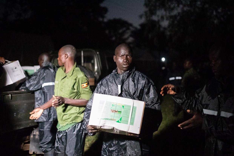 Oegandese soldaten laden dozen met pesticiden uit om vroeg in de ochtend te kunnen beginnen met het bestrijden van de sprinkhanenplaag.