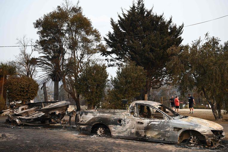 Door het vuur verwoeste auto's en een een boot in Lake Conjola in New South Wales.