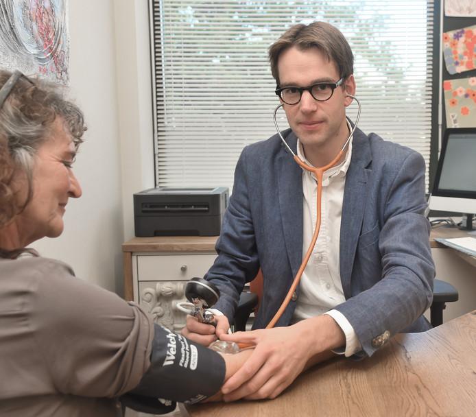 Huisarts Arjan Roest meet de bloeddruk van mevrouw Leendertse