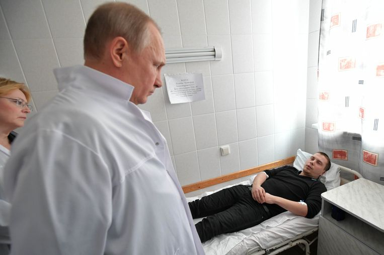 De Russische president Vladimir Poetin, voor de gelegenheid in witte doktersjas, bezocht vanochtend in een ziekenhuis de gewonden van de warenhuisbrand in de Siberische stad Kemerovo.  Daarbij vielen afgelopen weekeinde zeker 64 doden, van wie 41 kinderen. Beeld EPA