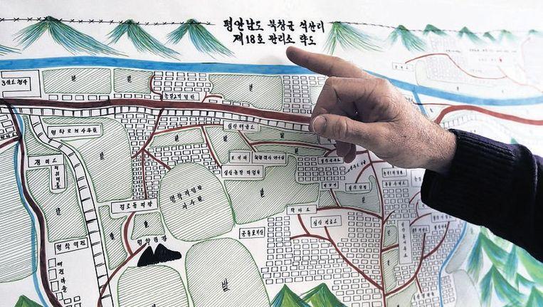 Een VN-medewerker toont een plattegrond van 'Werkkamp 18'. Beeld reuters
