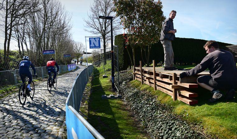 Terwijl renners de helling van de Oude Kwaremont verkennen, bouwen bewoners langs de route hun podiumpje om zondag de Ronde van Vlaanderen goed te kunnen zien. Beeld Marcel van den Bergh
