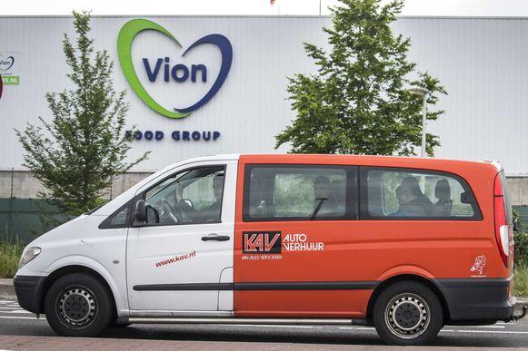 Uitzendkrachten verlaten in een busje het slachthuis van Vion in Groenlo.