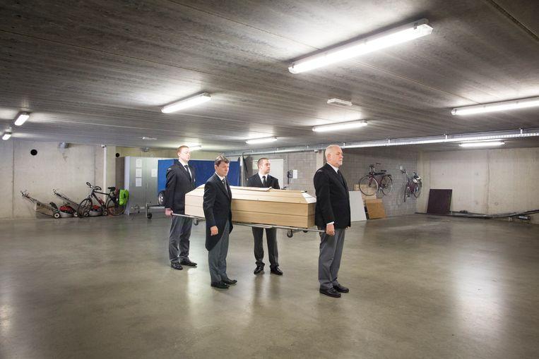 De dragers van de Vlaamse uitvaartonderneming Pues oefenen met de kist in de garage van hun familiebedrijf. Beeld Lieve Blancquaert