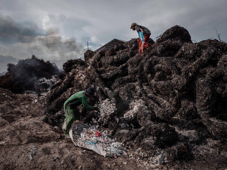 Afvalverwerkers treffen voorbereidingen om plasticafval te verbranden op een vuilstortplaats in Mojokerto op Oost-Java, Indonesië. Beeld Getty Images