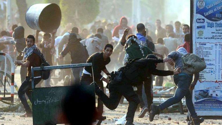 Een Egyptische politieagent probeert een student op te pakken bij de derde dag van onlusten in Caïro Beeld afp