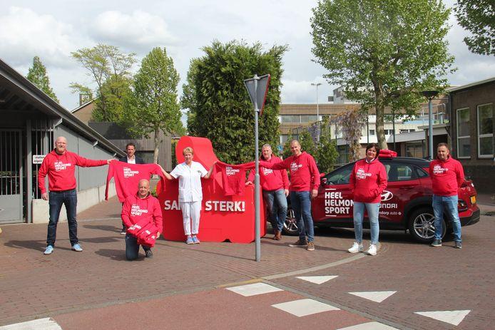 De stichting Heel Helmond Support en directeur Leon Vlemmings delen hoodies uit aan het Elkerliek-personeel.