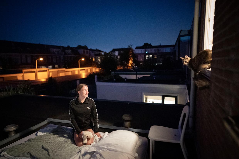 Lies Kop (17)  maakt haar slaapplaats gereed voor overnachting op de uitbouw. Rechts in het badkamerraam poes Goofy.