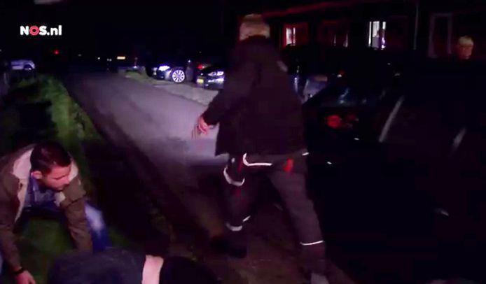 Videostill NOS: De vrouw die de auto blokkeerde is zojuist aan de kant getrokken door een agent in burger. Een andere man rent achter de auto aan.